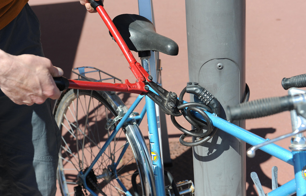 Bike theft. Bike fastened to a post and man cutting a bike lock with a bolt clipper